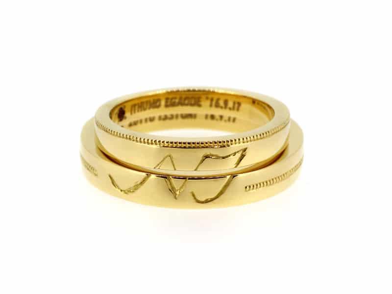 重ねるとおふたりのイニシャルのマークになる結婚指輪とミルの組み合わせ 結婚指輪2本トータルでデザインされています。
